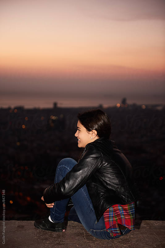 Young smiling woman sitting against of evening cityscape by Guille Faingold for Stocksy United