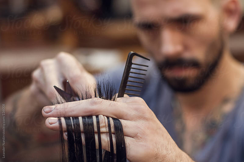 Close up of a hairdresser cutting hairs between his fingers by Leander Nardin for Stocksy United