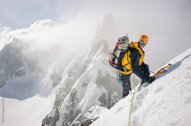 Mountaineer climbing a snow ridge at high altitude by RG&B Images for Stocksy United