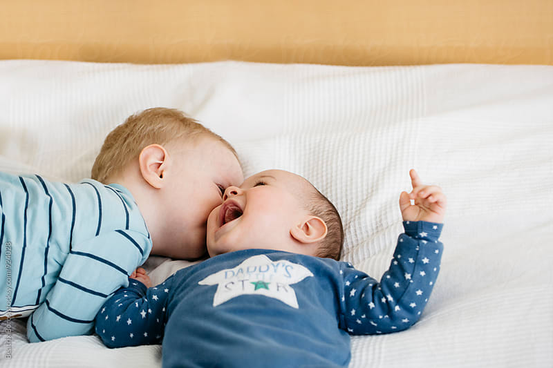 Brother kissing his laughing sibling by Beatrix Boros for Stocksy United