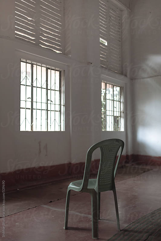 An empty chair facing the window. by Shikhar Bhattarai for Stocksy United