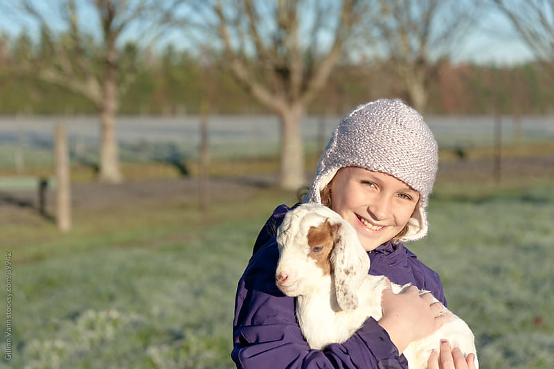 young girl with goat by Gillian Vann for Stocksy United