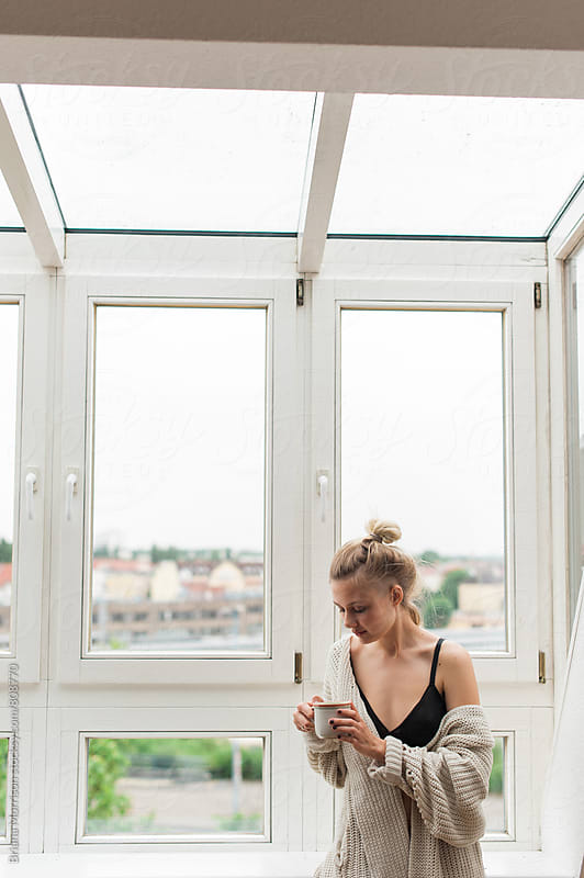 Young Blond Woman With a Mug of Tea in a Large Window by Briana Morrison for Stocksy United