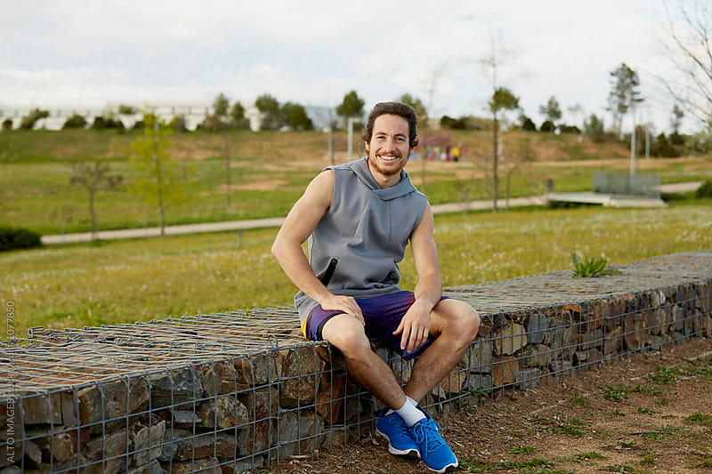 Happy Male Athlete Sitting On Gabion Wall by ALTO IMAGES for Stocksy United