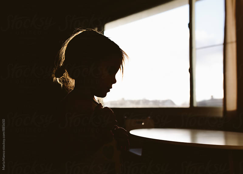 Silhouette profile of little girl in home by Maria Manco for Stocksy United