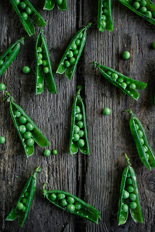 Pea pods open revealing the peas, on a wooden background.  by Darren Muir for Stocksy United