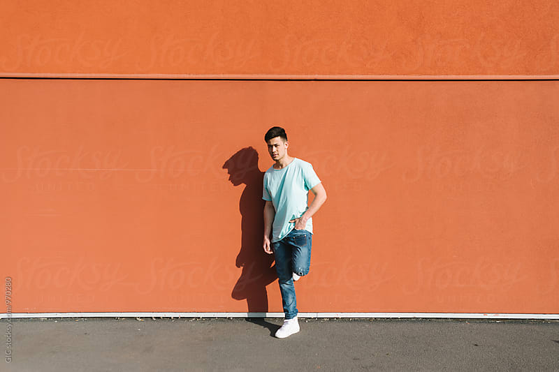 Cool asian man portrait against big orange wall by Simone Becchetti for Stocksy United