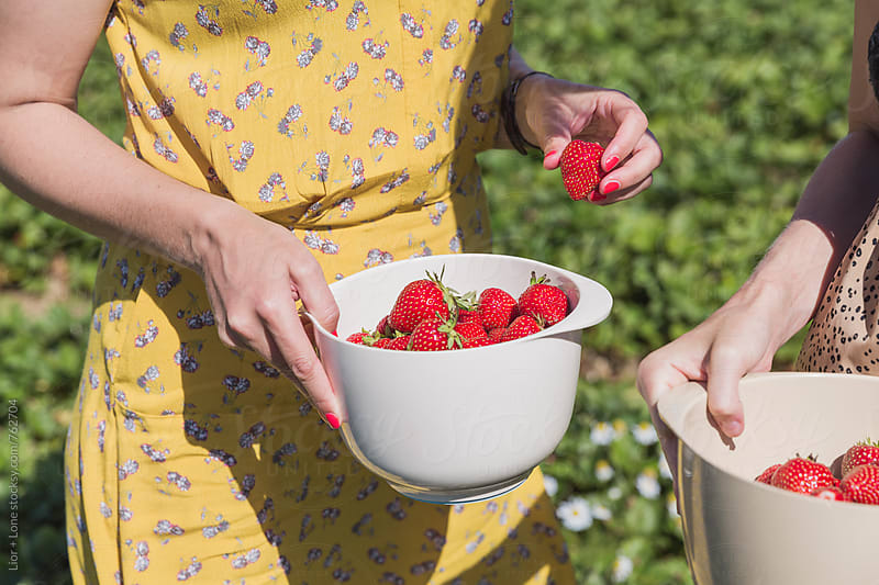 Friends with freshly picked strawberries in containers by Lior + Lone for Stocksy United