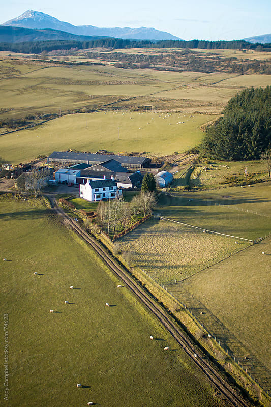 An aerial view of a sheep farm in Scotland, with mountains and fields in view. by Andy Campbell for Stocksy United