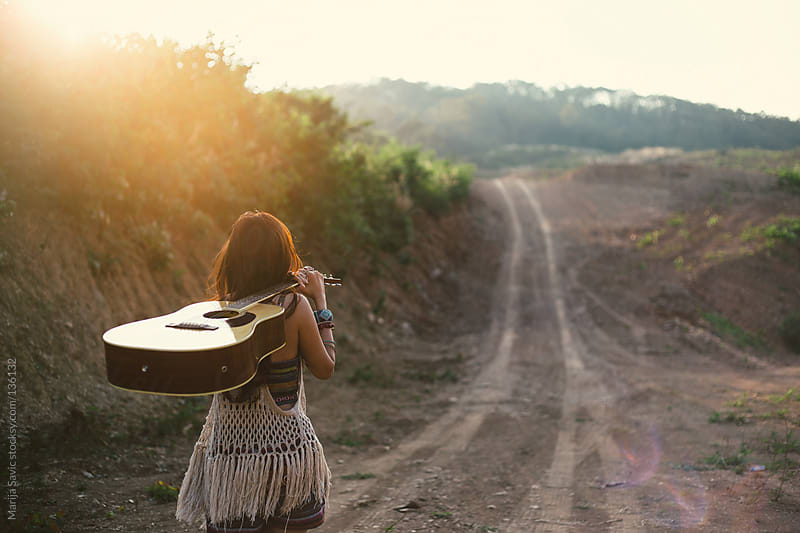 Hippie woman carrying her guitar in the mountains.  by Marija Savic for Stocksy United
