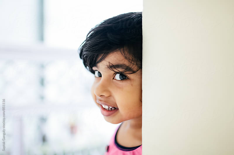 Little girl peeking from behind a wall and smiling by Saptak Ganguly for Stocksy United