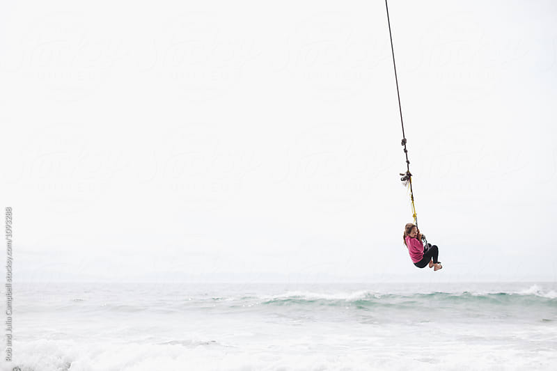 Young girl flying over ocean water on rope swing by Rob and Julia Campbell for Stocksy United