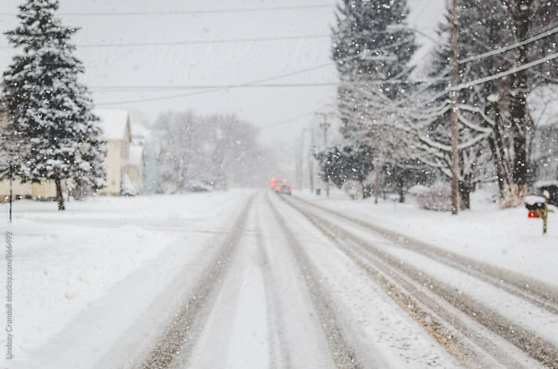 Snowy street with out of focus cars driving away by Lindsay Crandall for Stocksy United