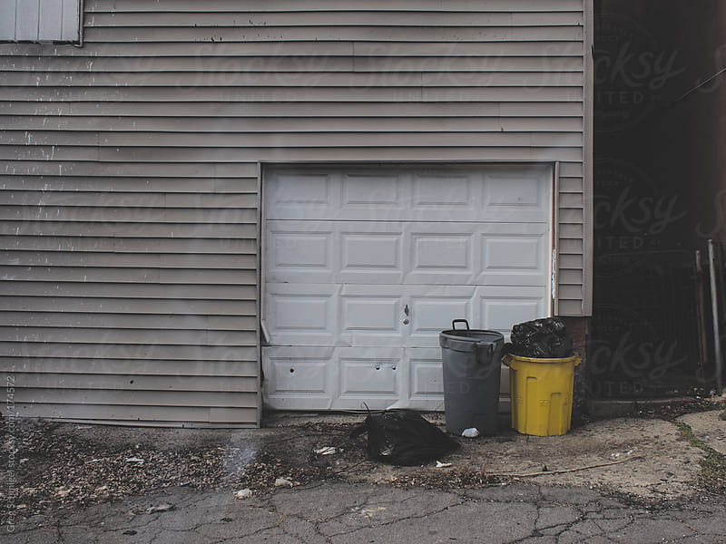 An urban scene of trash cans and a garage door in an alley by Greg Schmigel for Stocksy United
