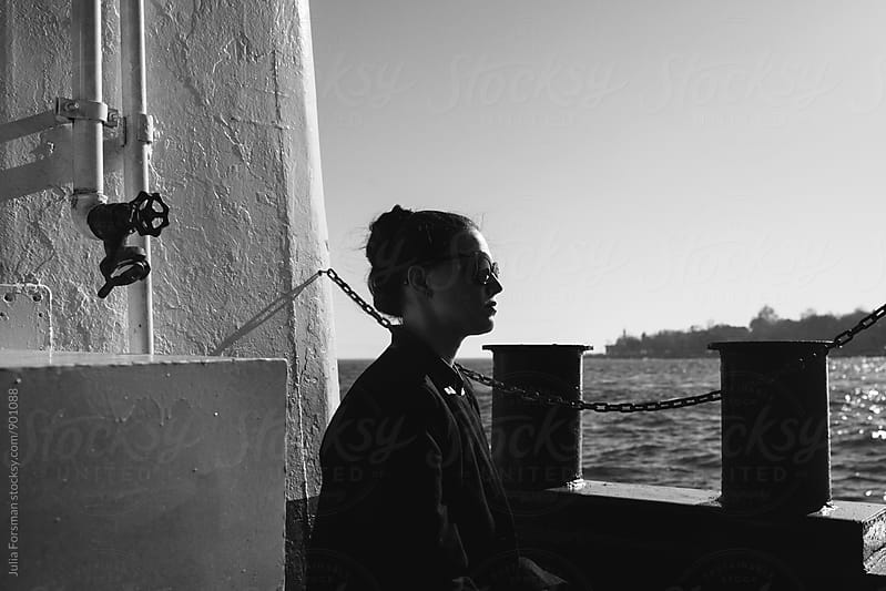 Woman sat on the deck of a ferryboat. by Julia Forsman for Stocksy United