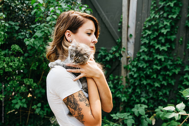young woman holding cute cat outdoors in front of ivy wall by Jesse Morrow for Stocksy United