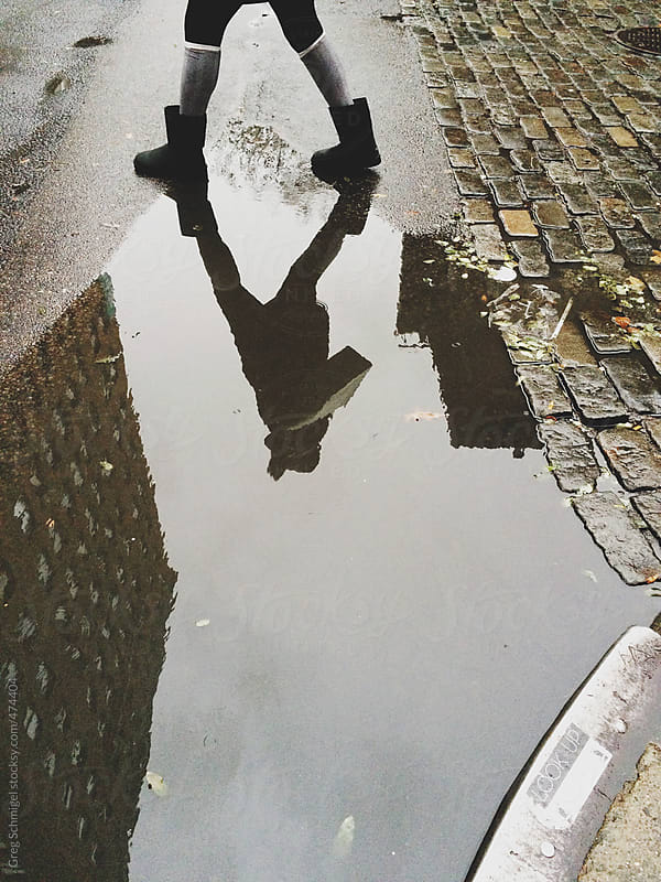 Reflection a woman stepping over a puddle of rain in New York City by Greg Schmigel for Stocksy United