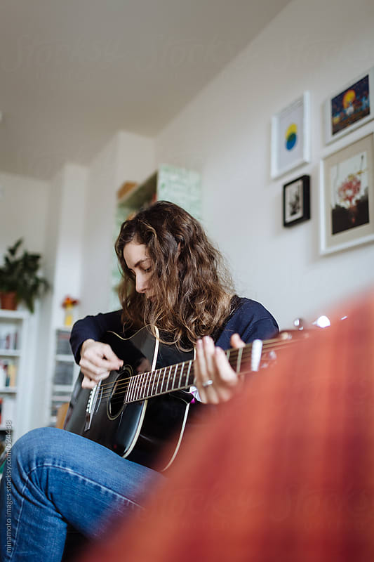 Pensive Woman Playing Guitar by minamoto images for Stocksy United