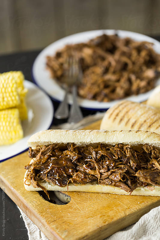 Shredded pulled beef in a panini bread roll sandwich by Kirsty Begg for Stocksy United