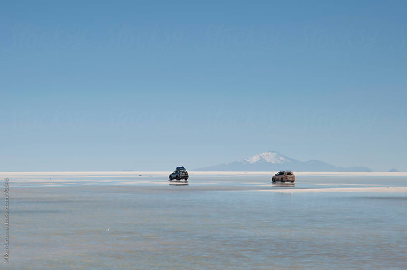 Two overland trucks crossing the salt flats in Bolivia. by Mike Marlowe for Stocksy United