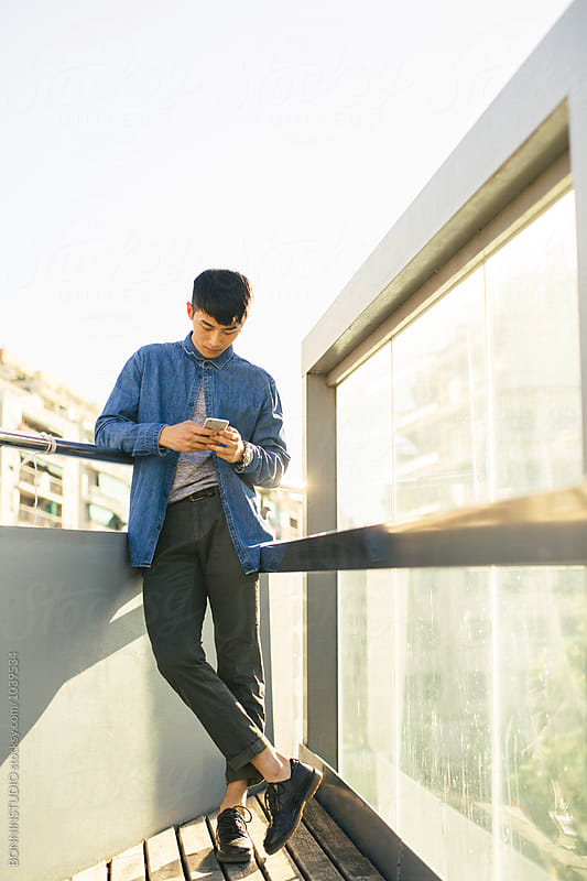 Stylish young asian man using a mobile phone in the street. by BONNINSTUDIO for Stocksy United