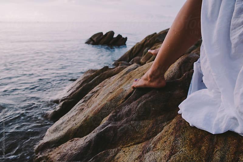 Woman's legs on the rocky shore. by Marija Savic for Stocksy United