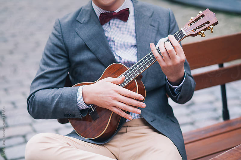 Young man playing guitar or ukelele while sitting on a bench  on a cobblestone street by Ivo de Bruijn for Stocksy United