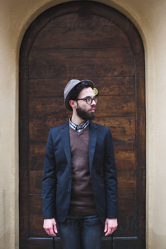 Man with beard standing at the door of his house by michela ravasio for Stocksy United