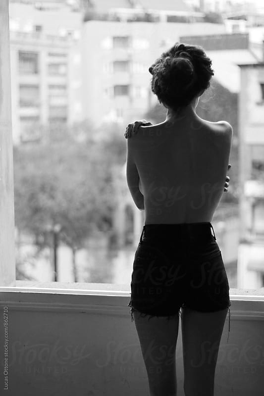 From the back: topless woman looking outside the window by Lucas Ottone for Stocksy United