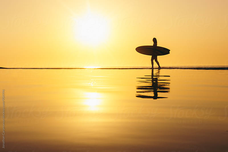 Young woman surfer walking along waters edge with reflection at golden hour by Jonathan Caramanus for Stocksy United