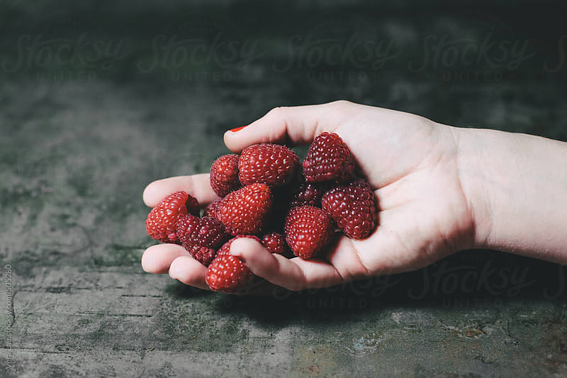 Hand holding a handful of raspberries by Vera Lair for Stocksy United
