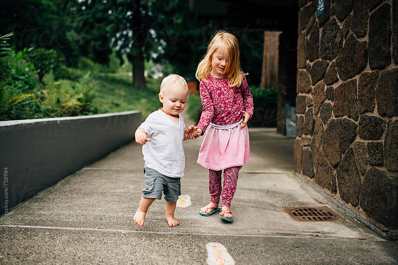 Two young Siblings happily walk hand in hand by a stone building by Amanda Voelker for Stocksy United