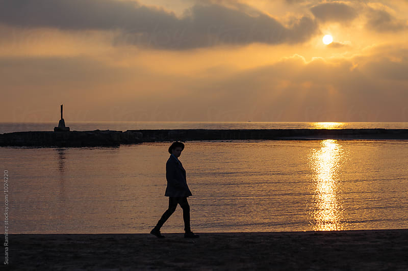 Silhouette man walking along the beach by Susana Ramírez for Stocksy United