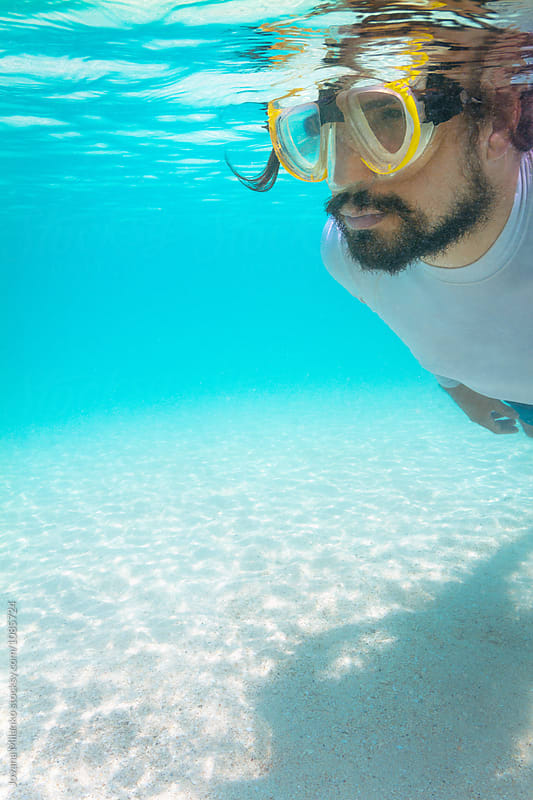 Man snorkeling underwater in tropics over the white sand by Jovana Milanko for Stocksy United