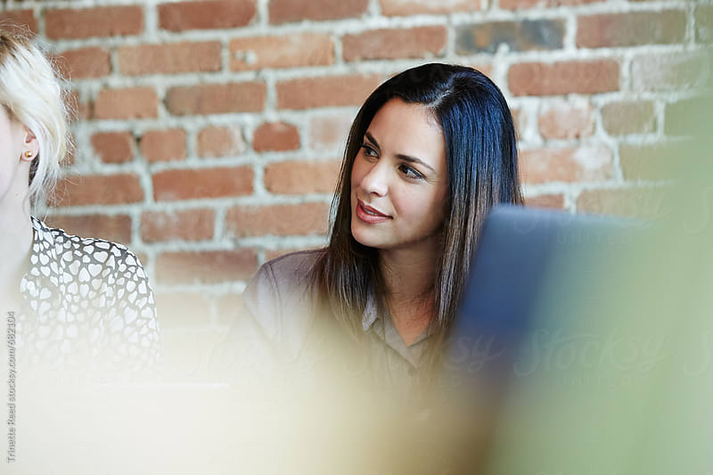 Close-up portrait of millennial Hispanic businesswoman in meeting by Trinette Reed for Stocksy United