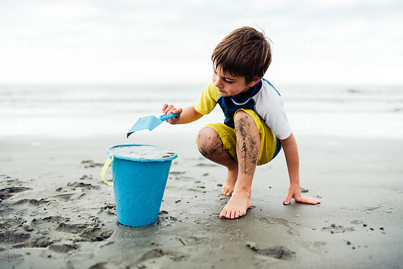 little boy playing with bucket and spade on beach by Léa Jones for Stocksy United