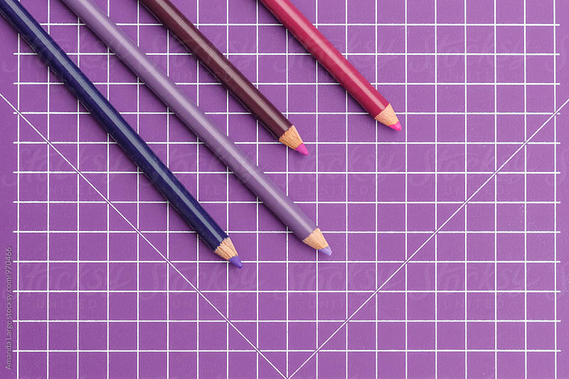 purple coloured pencils on a purple grid background by Amanda Large for Stocksy United