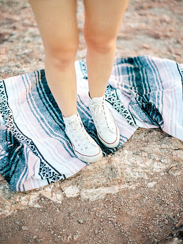 Close up of sneakers on blanket by Daniel Kim Photography for Stocksy United