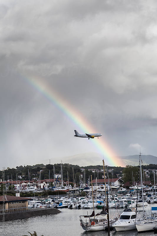 Airplane landing in Irun airport with a rainbow and rainy clouds by Ivan Bastien for Stocksy United
