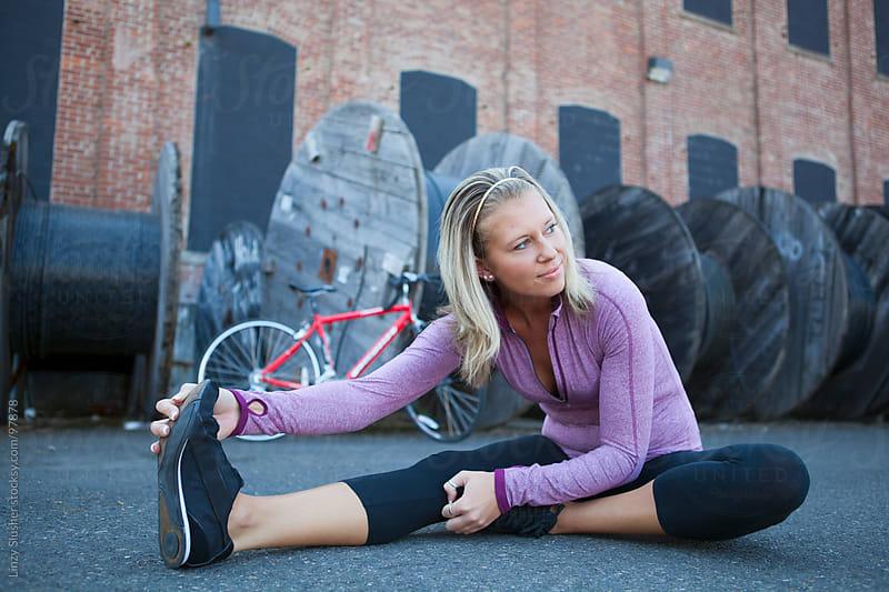 Athletic female stretches in urban background by Linzy Slusher for Stocksy United