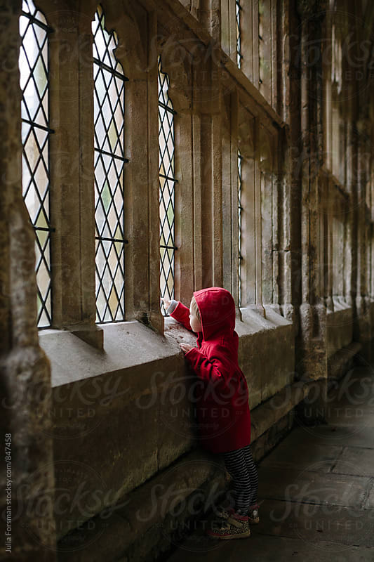Little girl pointing out of a window in a beautiful stone Gothic cloister. by Julia Forsman for Stocksy United