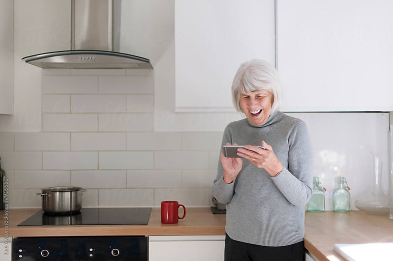 happy senior woman in her kitchen using an electronic mobile device by Lee Avison for Stocksy United