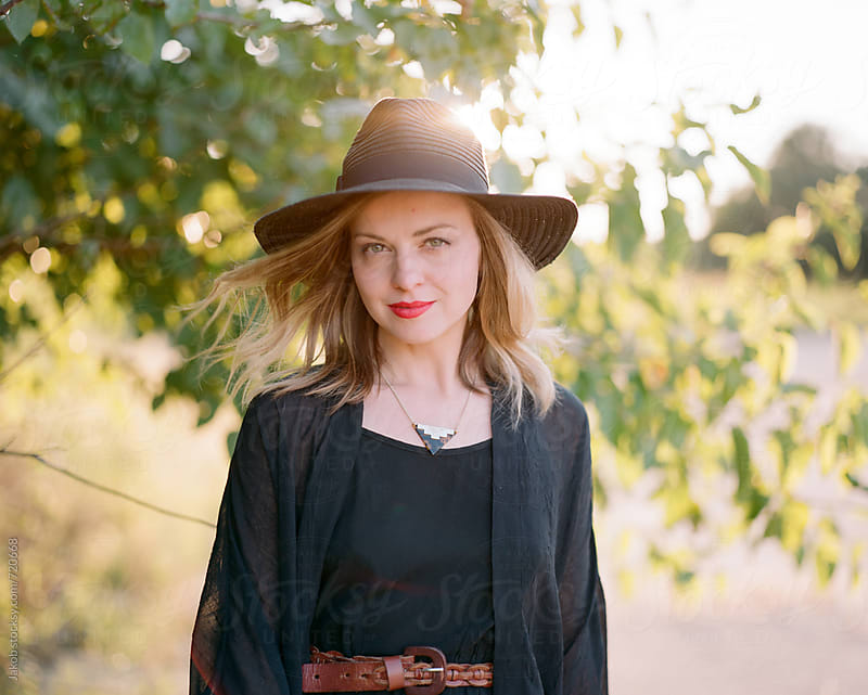 Beautiful and fashionable woman standing outside by a tree by Jakob for Stocksy United