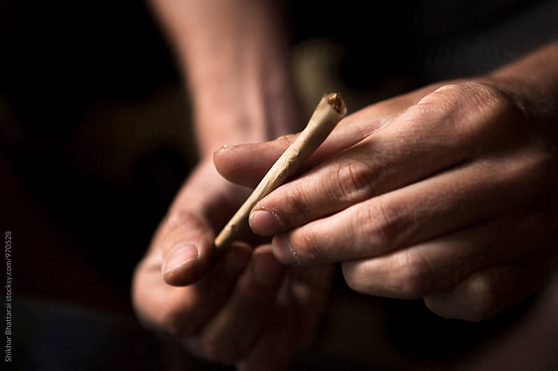 Close up of Hands of a man rolling a joint. by Shikhar Bhattarai for Stocksy United