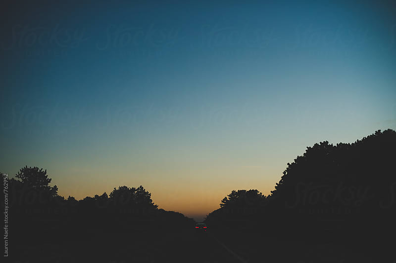 Car driving down road during sunset by Lauren Naefe for Stocksy United