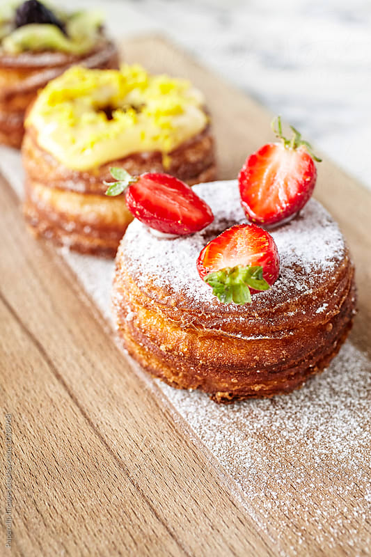 Cronut with strawberry and powdered sugar by Paperclip Images for Stocksy United
