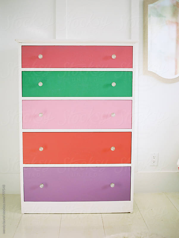 rainbow colored bureau or chest of drawers in white room by wendy laurel for Stocksy United