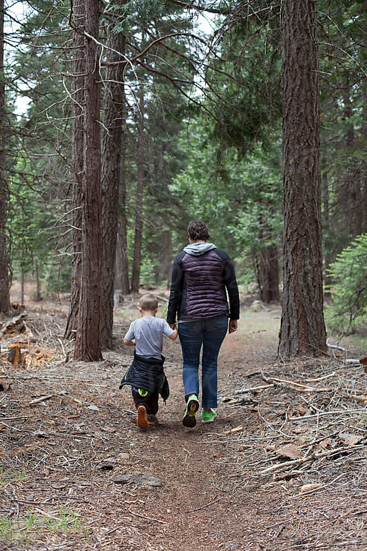 Mom and five year old son hold hands while hiking on the Pacifc Crest Trail by Carleton Photography for Stocksy United