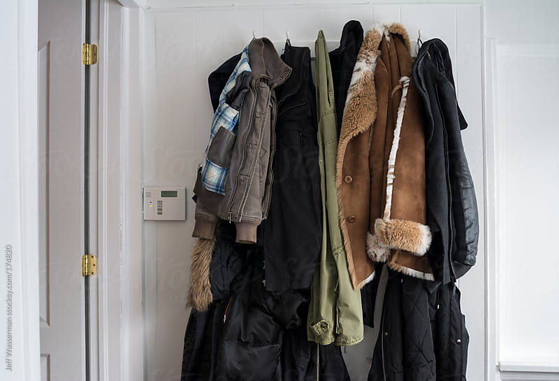 Coats Hanging on Rack and Security Alarm Panel by Jeff Wasserman for Stocksy United