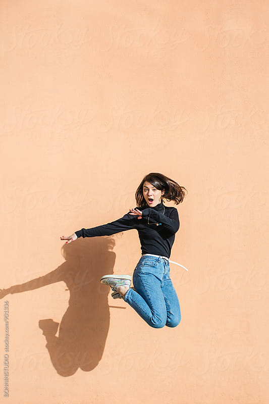 Brunette girl jumping in front of a wall.  by BONNINSTUDIO for Stocksy United